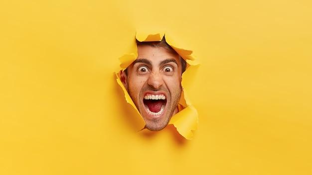 Сердитое мужское лицо через отверстие желтой бумаги. возмущенный мужчина просовывает голову сквозь разорванный фон