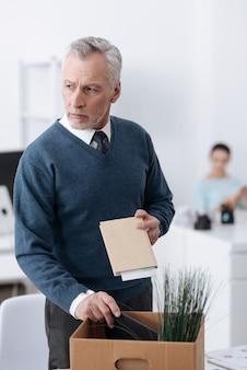 彼の職場の近くに立っている間、左手にノートを保持して横向きに見ている怒っている男性