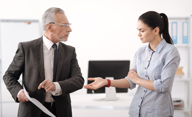 Angry male person wearing costume holding document in right hand while looking at his worker