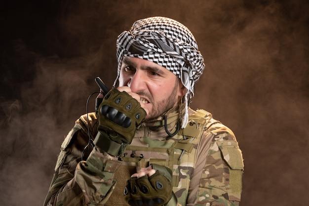 어두운 벽에 설정된 라디오를 통해 이야기하는 위장에 화가 난 남성 군인