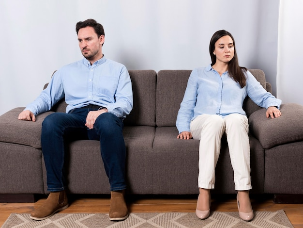 Angry male and woman sitting on the couch