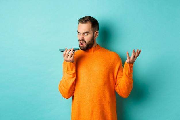화난 사람이 스피커폰에 주장하고, 미친 얼굴로 음성 메시지를 녹음하고, 주황색 스웨터에 밝은 파란색 배경 위에 서 있습니다.
