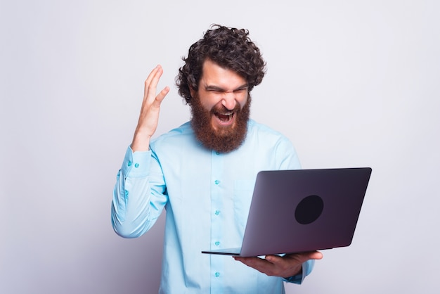 Angry man in blue shirt having trouble at work, man screaming at laptop
