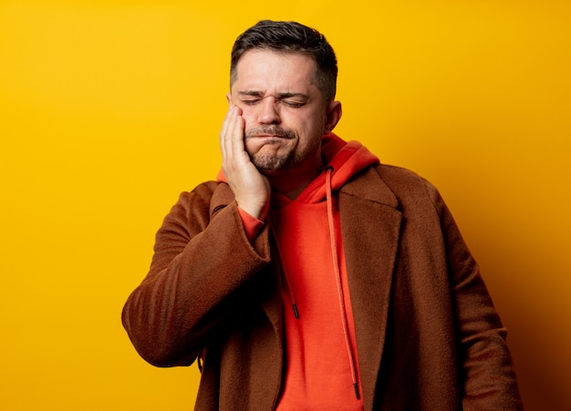 Angry man in coat with tooth pain on yellow wall