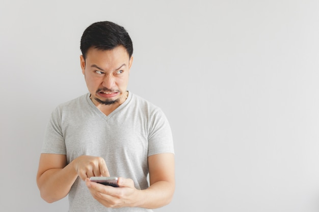 Angry man in grey t-shirt get mad on the smartphone.