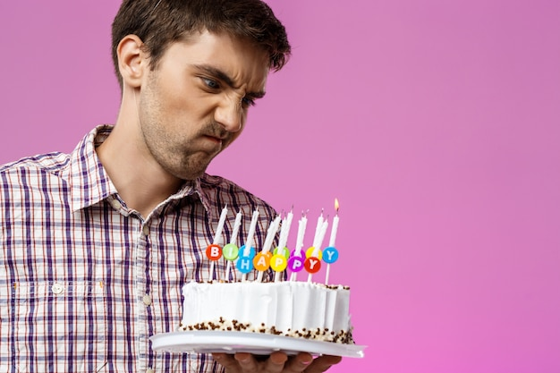 Angry man holding birthday cake with one not blow out candle.