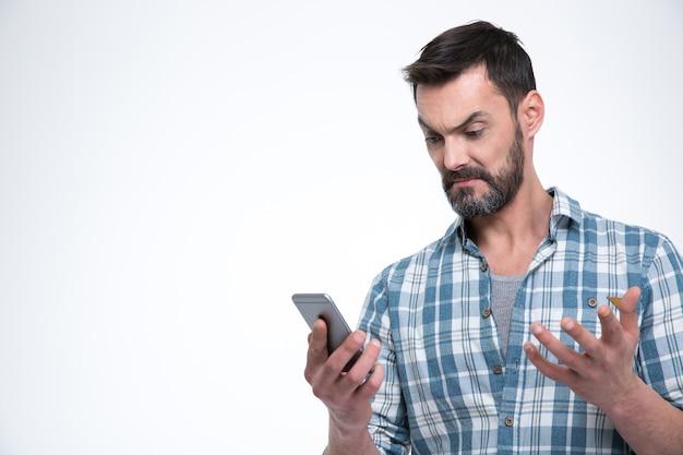 Злой человек, держащий смартфон, изолированный на белой стене