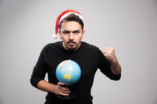 주먹을 표시 하 고 지구본을 들고 산타의 모자에 성 난 남자.