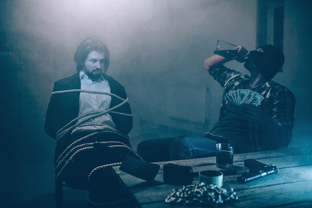 Злой человек в номере сидит привязанный к стулу. он смотрит на похитителя. мужчина в маске сидит рядом со своей жертвой и пьет алкоголь из бутылки. на столе цепочки, нож и лента.