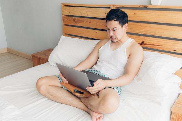 Angry man is working with his laptop on his bed. concept of freelancer problems.