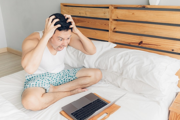 Angry man is working with his laptop on his bed.
