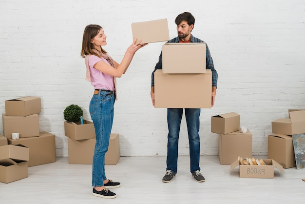 Angry man looking at her wife stacking the cardboard boxes over his hands