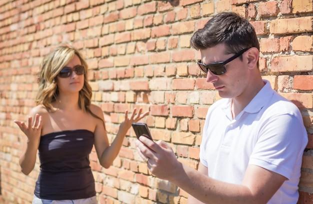Сердитый мужчина смотрит телефон и недоволен молодой женщиной вверх руками перед стеной на заднем плане. сосредоточьтесь на мужчине.