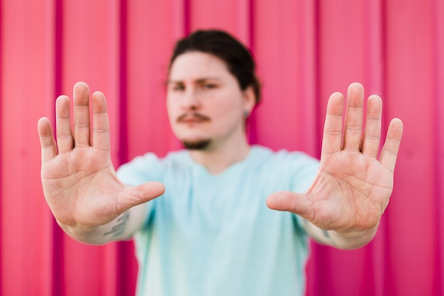 An angry man making stop gesture against red backdrop