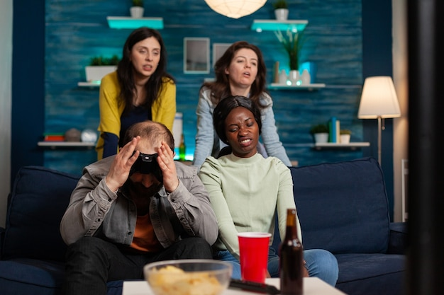 Angry man and multi ethnic friends upset after losing game competition, bonding and sitting on couch after drinking beer