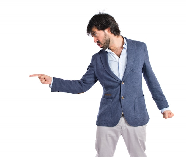 Angry man pointing somebody over isolated white background