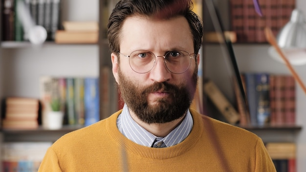 Angry man, rage. angry annoyed bearded man in glasses in office or apartment room looking at camera and hits table with his fist, pencils fly to sides. close-up view