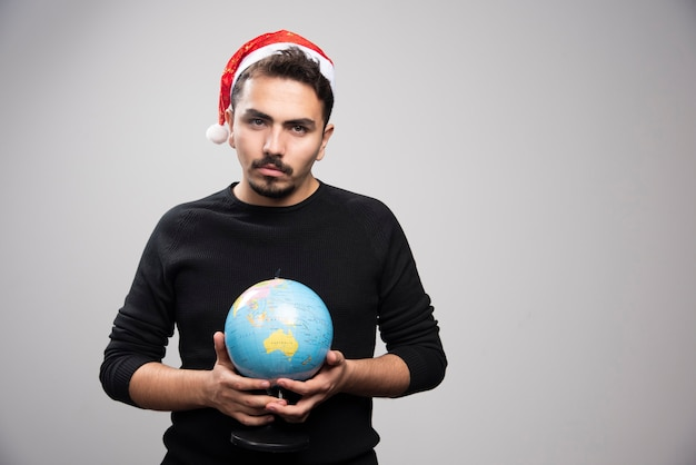 Angry man in santa's hat holding a globe.