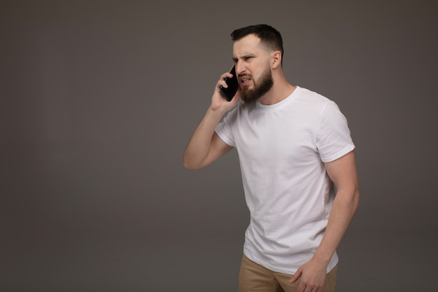 Angry man screaming on the phone isolated on a grey background