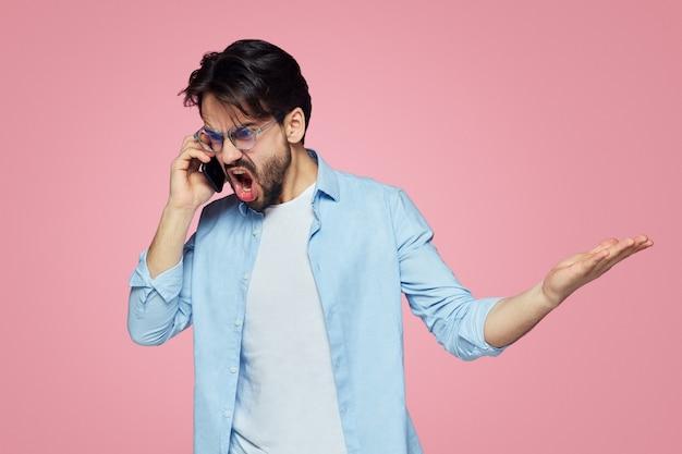 Злой человек громко кричит во время мобильного разговора