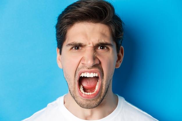 Злой человек кричит и смотрит с ненавистью, стоит безумно у синей стены