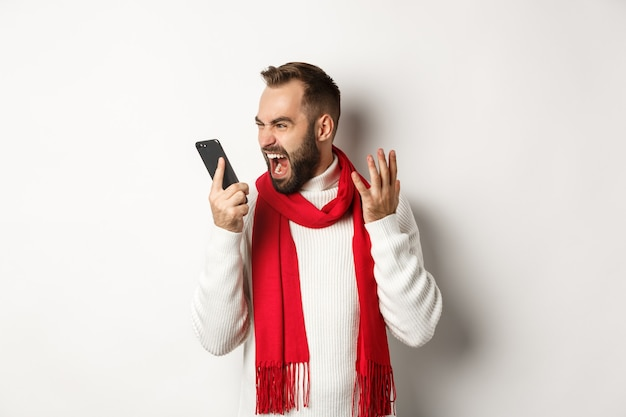 화난 남자가 화난 얼굴로 스마트폰에 소리를 지르며 흰색 배경에 화를 내며 서 있다