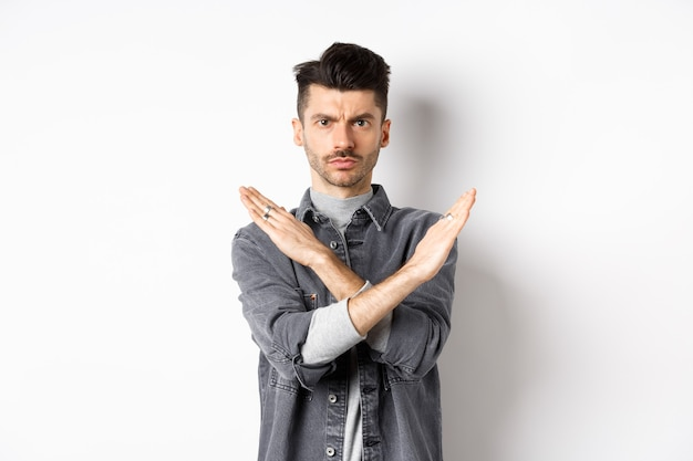 Angry man show cross gesture to stop or say no, frowning and looking serious, disagree and prohibit bad situation, standing on white background.