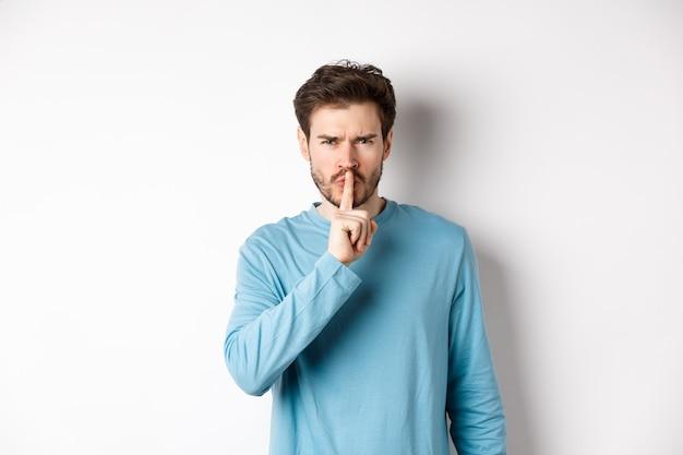 화가 난 남자는 카메라를 쉿 취하고 조용히 말하고, 찡그린 얼굴을하고, 입술에 손가락으로 흰색 배경 위에 서서 금기 제스처.