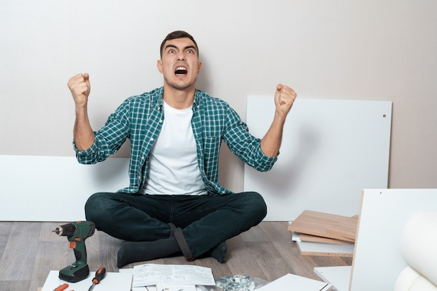 Angry man sitting on the floor with instructions for assembling furniture.