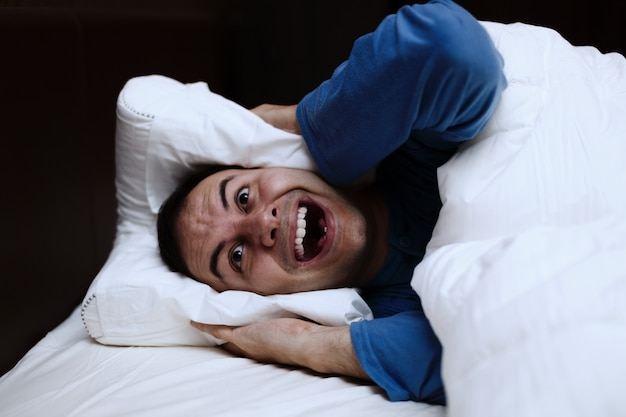 Angry man using a pillow to cover his ears