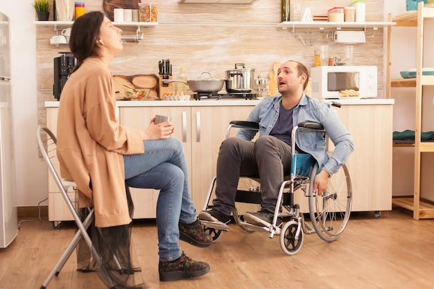 Angry man in wheelchair because of emotional difficulties with wife in kitchen. disabled husband arguing with spouse.