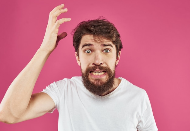 Angry man with beard holds hands near face and stress irritability.