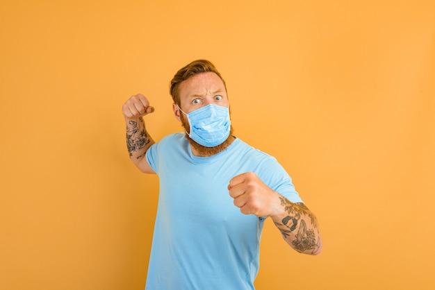 코비드에 대한 수염 문신과 마스크를 쓴 화난 남자는 싸우고 싶어한다