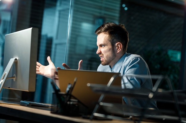 사무실에서 컴퓨터와 화난 사람