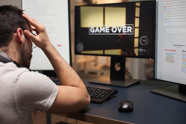 オンラインシューティングゲームで彼を失った後の眼鏡をかけた怒っている男。競争力のある男のためのゲームオーバー。
