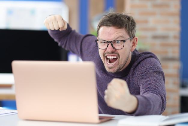 眼鏡をかけた怒っている男は、ラップトップモニターで彼の拳を振る。職場の概念における攻撃性とかんしゃく