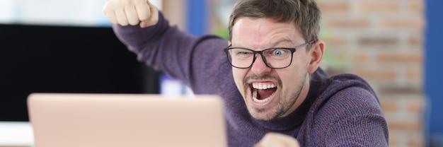 怒った眼鏡をかけた男は、ラップトップ モニターで拳を振る。職場のコンセプトにおける攻撃性とtanttanttant
