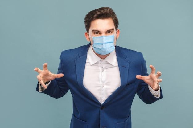 カメラを見て青いスーツのサージカルマスクを持つ怒っている男