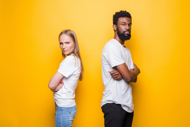 Angry man and woman being in fight and standing back to back with arms folded isolated over yellow wall