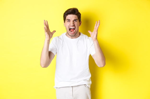 Angry man yelling and shaking hands, grimacing with hatred, standing hateful against yellow background. copy space