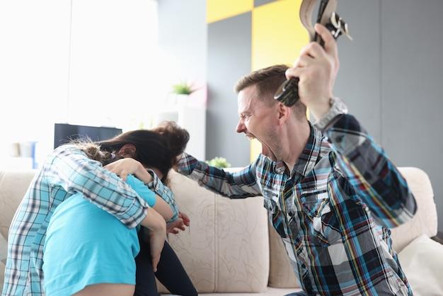 화난 남자는 그의 아내와 그의 손에 벨트를 들고 아이에게 고함