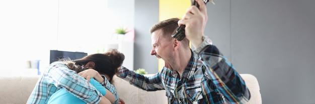 화난 남자는 그의 아내와 손에 벨트를 들고 있는 아이에게 소리친다