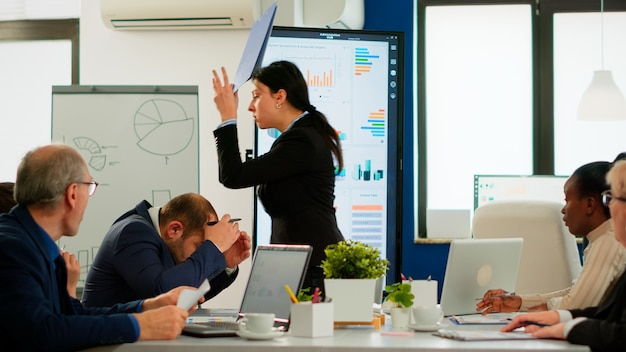 Angry manager woman arguing disagreeing about bad business contract, diverse colleagues having conflict dispute about document sitting in office desk during brainstorming partners working in boardroom