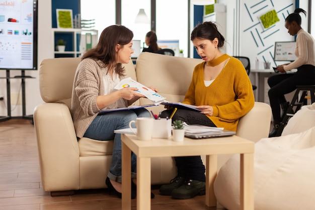 Сердитая женщина-менеджер кричит на сотрудника, не согласного с плохим деловым контрактом, сидя на диване за офисным столом