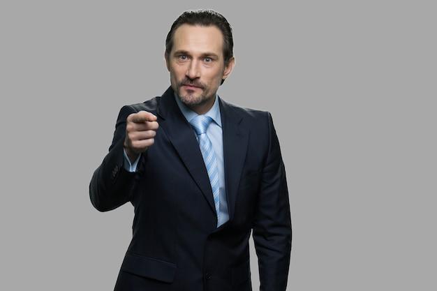 同僚と議論している怒っている成熟したビジネスマン。カメラに警告指を向ける厳格な雇用主の肖像画。灰色の背景に分離。