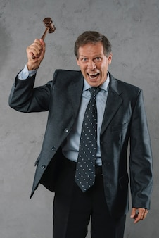 An angry mature male lawyer hitting with gavel against gray textured background