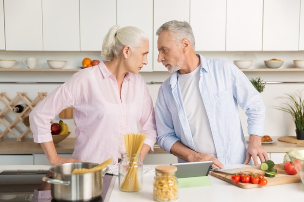 Angry mature man standing near mature serious woman at kitchen