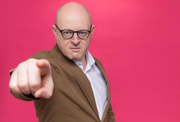 Uomo calvo di mezza età arrabbiato in vestito con gli occhiali che punta con il dito indice davanti in piedi sopra il muro rosa