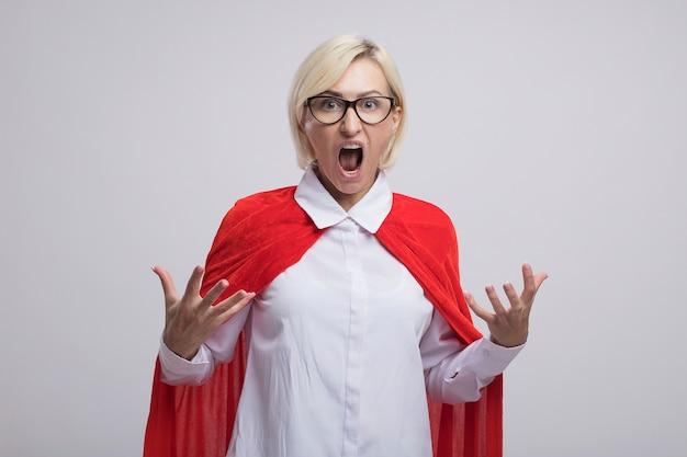 Donna supereroe bionda di mezza età arrabbiata in mantello rosso con gli occhiali guardando davanti tenendo le mani in aria urlando isolato sul muro bianco