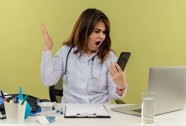 コピースペースのある孤立した緑の壁に電話を持って見ている医療ツールを備えたラップトップでデスクワークに座って聴診器で医療ローブを身に着けている怒っている中年の女性医師